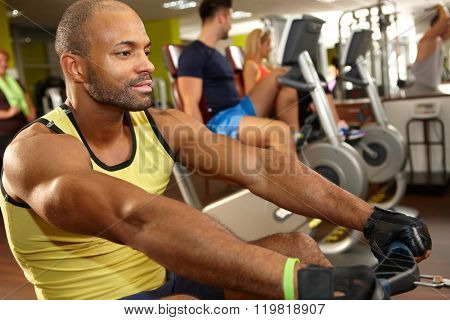 Young athletic black man training on rowing machine in gym.