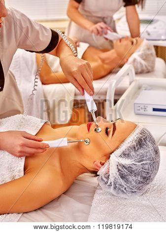 Group of friend women receiving electric galvanic face spa massage procedure by two beauticians at beauty salon.