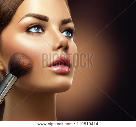 Makeup. Beauty model girl Applying Make-up  closeup. Cosmetic Powder Brush for Make up. Female with Perfect Skin. Blue eyes, Pink Lipstick. Isolated on Black Background. Beautiful woman face, Makeover