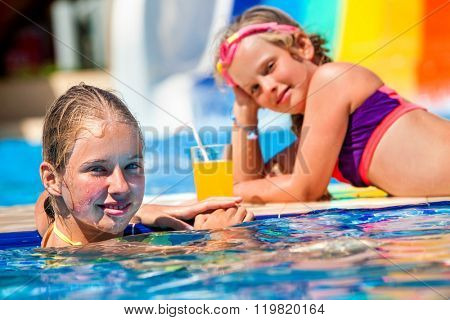 Children sisters on water slide at aquapark and drink juice. Summer holiday.