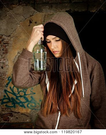 Drunk girl holding bottle of alcohol on  messy brick wall background. Soccial issue alcoholism.