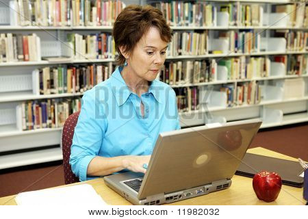 A pretty school librarian doing researh on-line in the media center.