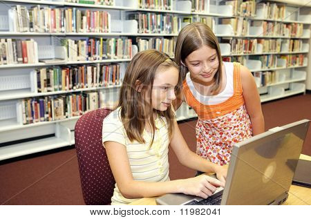 Two cute school girls doing research on-line in the school library.
