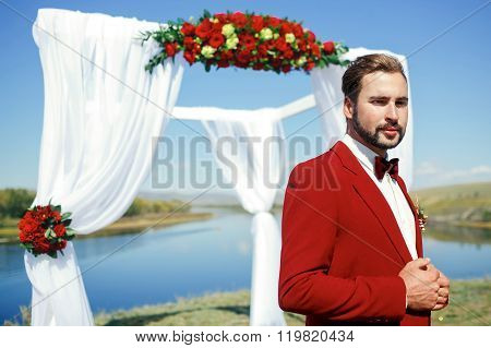 Groom in a red suit with bow tie