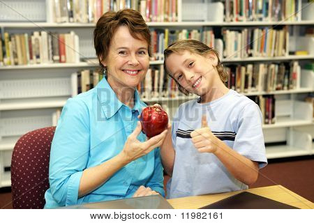 A school boy giving an apple to his teacher and a thumbs-up sign to the camera.