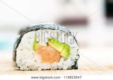 Sushi with salmon, avocado, rice in seaweed and chopsticks on wooden table. Japanese, Asian healthy food.