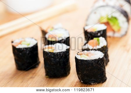 Sushi rolls with salmon, avocado, rice in seaweed and chopsticks on a wooden table. Japanese, Asian healthy food.