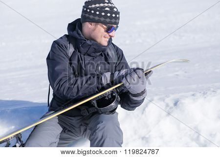 Man Cleaning Snowboard With Hand