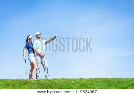 Young couple playing golf outdoors