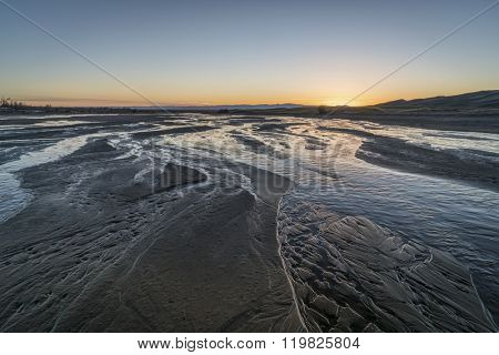 sunset over shallow Medano Creek disappearing in sand - Great Sand Dunes National Park, Colorado
