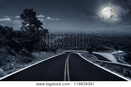 asphalt road in the mountains in the moonlight