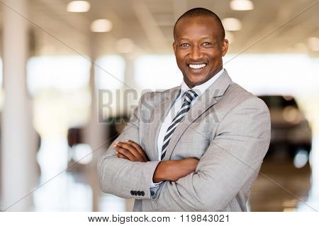 african car sales consultant with arms folded in showroom