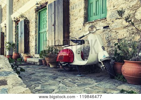 Old Scooter Parked By The Wall In The Empty Street Of Karpathos, Greece.