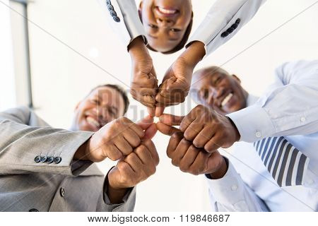 underneath view co-workers with thumbs joined together