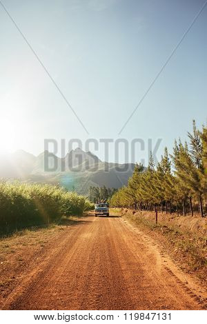 Distant Car Approaching On A Rural Dirt Road On A Sunny Day