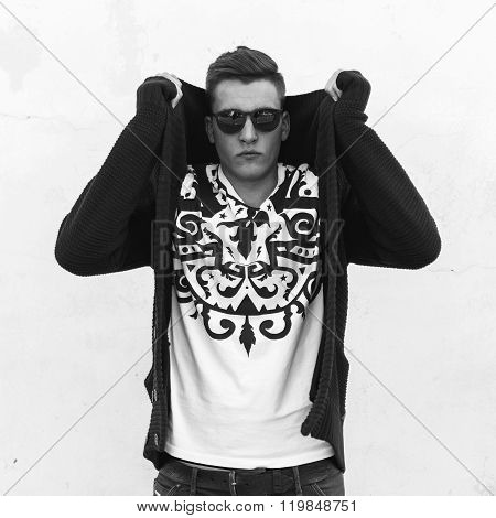 Black And White Portrait Of A Young Handsome Guy In Sunglasses And A Sweater Near A White Wall