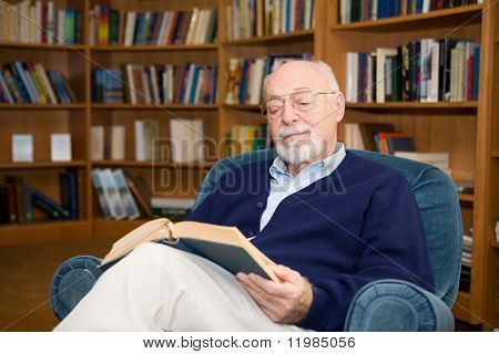 Handsome senior man relaxing with a good book.  Plenty of room for text.