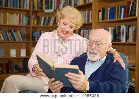 Senior par disfrutar juntos de un buen libro en la biblioteca.