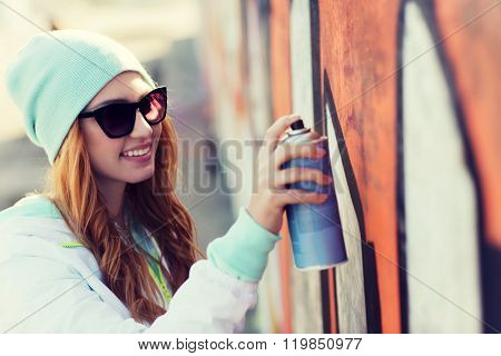 people, art, creativity and youth culture concept - young woman or teenage girl drawing graffiti with spray paint on street wall