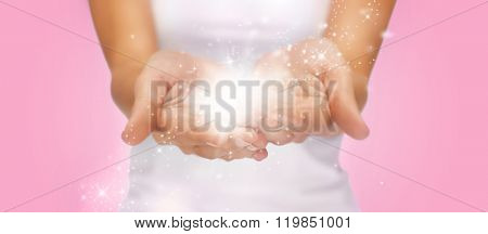 people and magic concept - close up of twinkles or fairy dust on female cupped hands over pink background