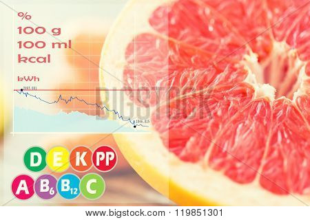 healthy eating, food, fruits and diet concept - close up of fresh juicy grapefruit slice on table with calories and vitamin chart