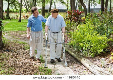 Elderly father and adult son out for a walk in the park.