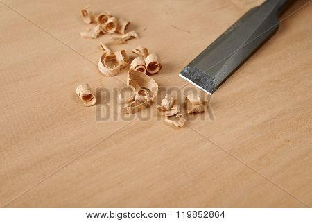 Woodworking Tool. A Chisel With Shavings On Workbench.