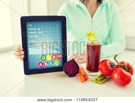 healthy eating, technology, diet and people concept - close up of woman hands holding tablet pc computer with calories and vitamins chart, vegetables