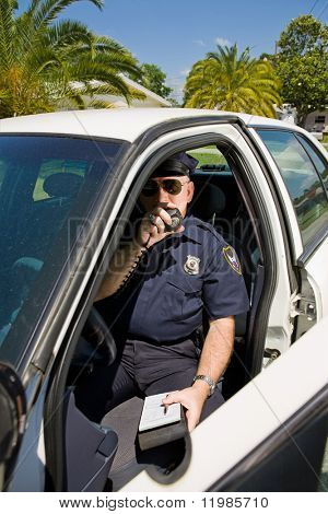 Police officer in his car calling in a license number on his radio.