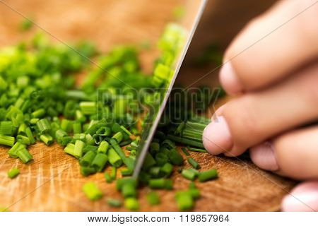 healthy eating, cooking, vegetarian food, kitchenware and people concept - close up of woman chopping green onion with knife on wooden cutting board