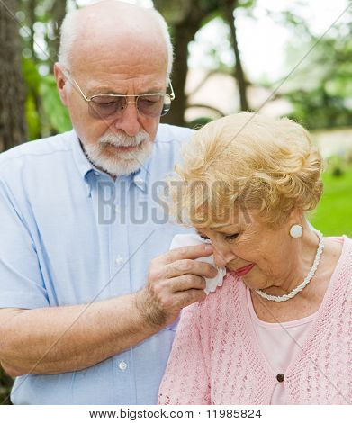 Sad senior lady cries while her husband wipes her tears.  Focus on the woman.