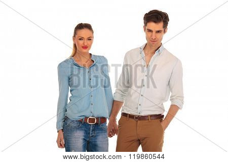 beautiful couple posing in white isolated studio background holding hands. the man is looking at the camera with one hand in pocket.