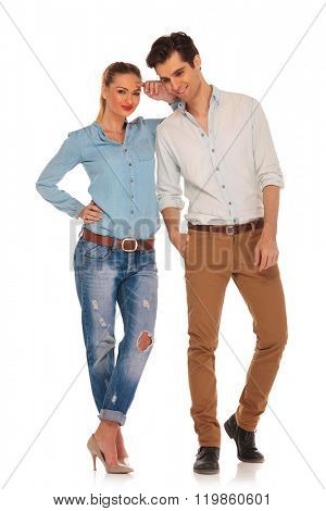 cute couple posing in white isolated studio background. woman with legs crossed looking at the camera while resting arm on his shoulder. man with hand in pocket looks down