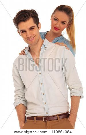 boy posing for the camera with both hands in pockets while girlfriend is holding him from behind in isolated studio background