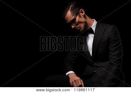 portrait of classy man in black tux wearing glasses posing in dark studio background looking down