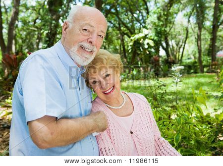 Loving senior couple outdoors in a beautiful natural setting.  Plenty of room for text.