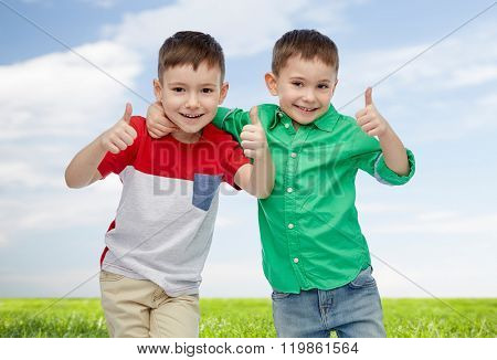 childhood, fashion, friendship, gesture and people concept - happy smiling little boys showing thumbs up over blue sky and green field background
