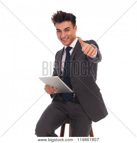young business man holding a tablet and making the ok thumbs up hand sign on white background