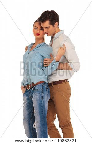 beautiful couple posing embraced in isolated studio background. she is looking at the camera while he is holding her from behind.