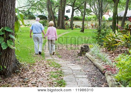 Senior couple strolling down a garden path together.  A metaphor for life's journey.
