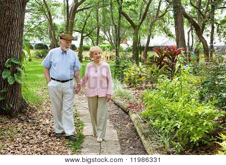 Senior couple walking through the park together.