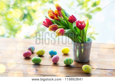 easter, holidays, tradition and object concept - close up of colored easter eggs and tulip flowers in tin bucket on wooden table over green natural background