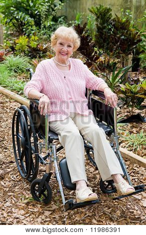Beautiful senior lady smiling outdoors in her wheelchair.  Full body view