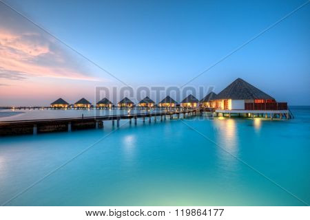 Water villas on Maldives resort island in sunset