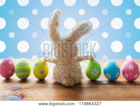 easter, holidays, tradition and object concept - close up of colored easter eggs and bunny over blue polka dot background