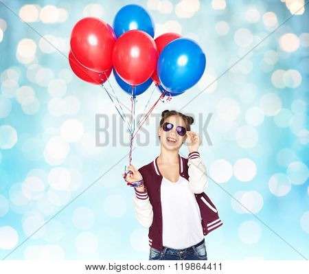 people, teens, holidays, party and summer concept - happy smiling pretty teenage girl in sunglasses with helium balloons over blue holidays lights background
