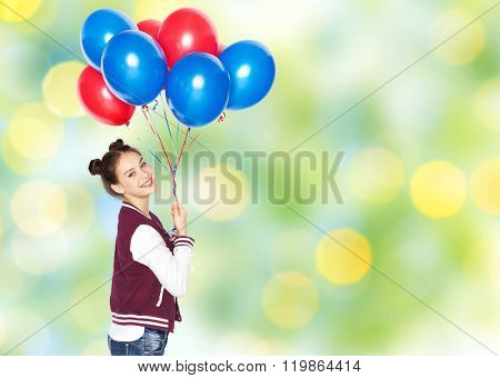 people, teens, holidays and party concept - happy smiling pretty teenage girl with helium balloons over green summer lights background