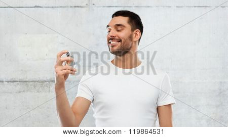perfumery, beauty and people concept - happy smiling young man with male perfume over gray stone wall background