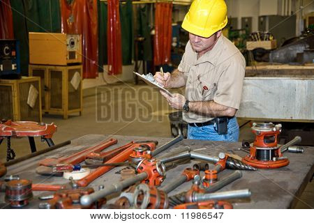 Auditor taking inventory of tools in an industrial factory.  Welding equipment is visible in the background.