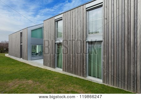 Exterior of a modern house in concrete and wood, lawn